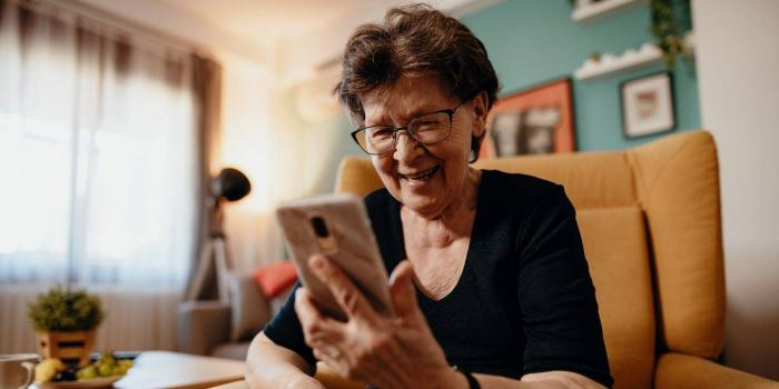 woman smiling at smartphone in her hand