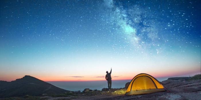 camper waving at a night sky