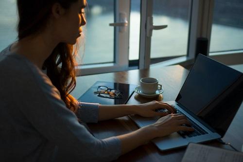 Woman sitting at laptop writing