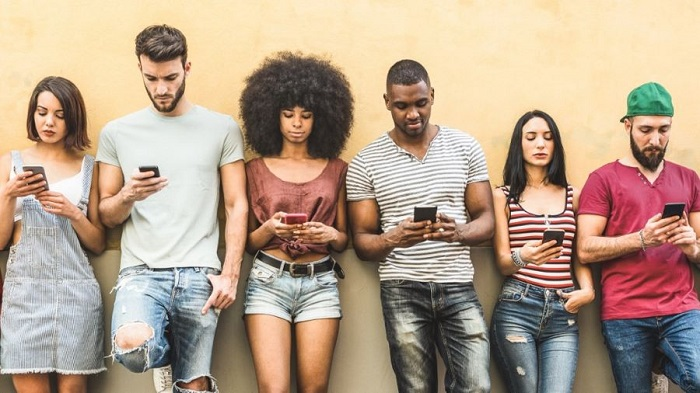 Line up of people looking at smartphones