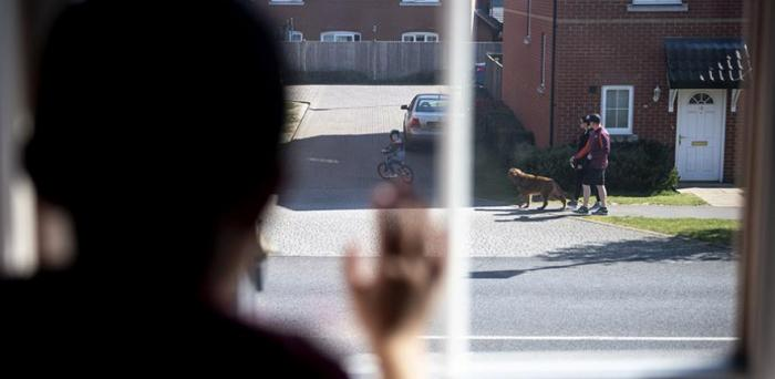 Young boy peers out of his bedroom window during the coronavirus lockdown in the UK in April.  Credit: Benjamin Cooper