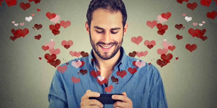 man looking at phone from which illustrated hearts are fluttering out
