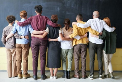 A line of people all holding each other across the shoulders
