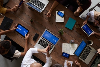 Board Meeting Image people with laptops leaning on a wooden table
