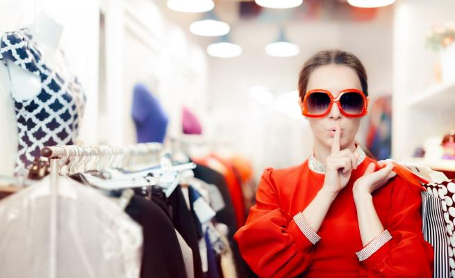 Woman in clothing store saying 'shush' and putting a finger to her lips