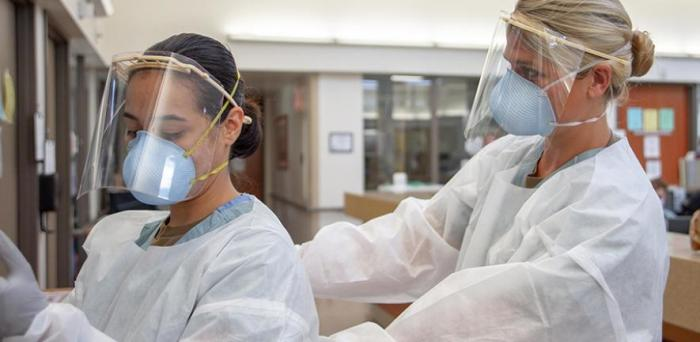Medical personnel don PPE before entering a COVID-19-positive, non-critical patient's room.  Credit: Official US Navy Page