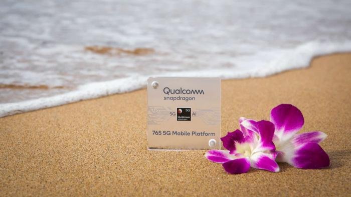 Qualcomm Snapdragon marker on a beach with a flower - ocean waves in the background