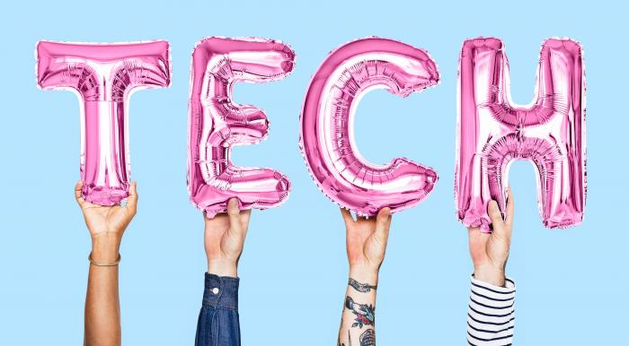 hands holding balloons spelling out the word tech