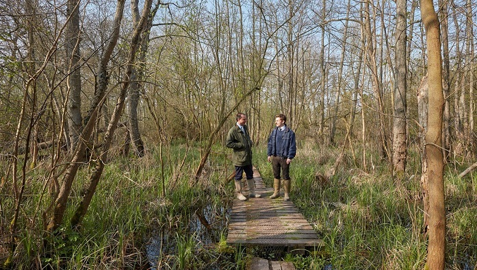 Two men standing in the woods and talking