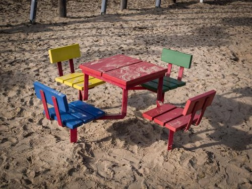empty table and chairs on a sandy beach