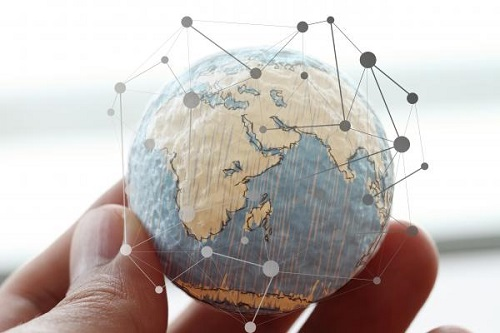 fingers hold globe with pinpoints