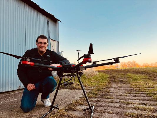 man crouching next to a commercial drone