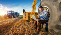 Man sitting on wheel of farm machinery in field with tractor in the background- sale of YAGRO Ltd to Frontier Agriculture
