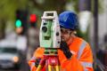 Man in orange high vis doing surveying work