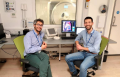 Psychiatrist Dr Emanuele Osimo (left) with cardiologist Dr Antonio De Marvao in front of the 3T Magnetic Resonance Imaging (MRI) scanner used for the study in the Robert Steiner MR Unit (Medical Research Council London Institute for Medical Sciences and Imperial College London).