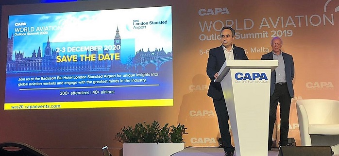 podium at World Aviation Summit 2019 with 'save the date' on the screen for 2020 event